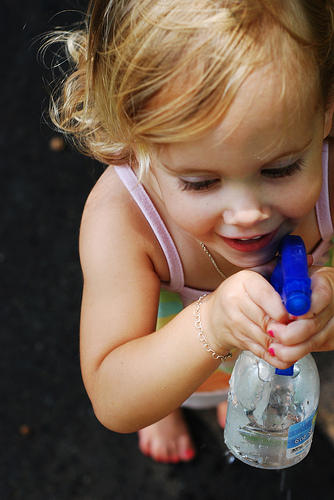 little girl with spray bottle