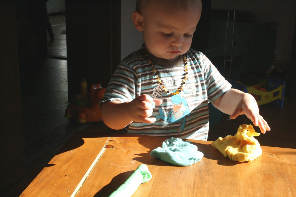baby exploring play dough