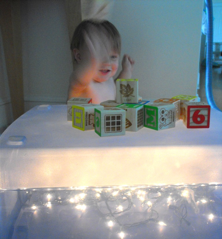Joshua plays with blocks on our homemade light box