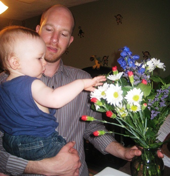 Baby pets his flowers
