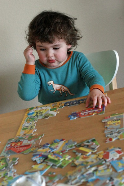 preschooler doing a puzzle at the table