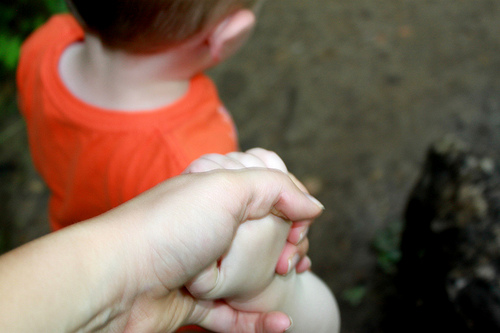 child holding hands with parent