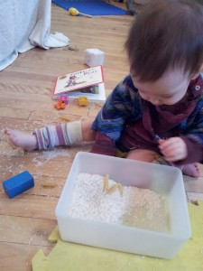 Baby focussed on playing with a box of rice